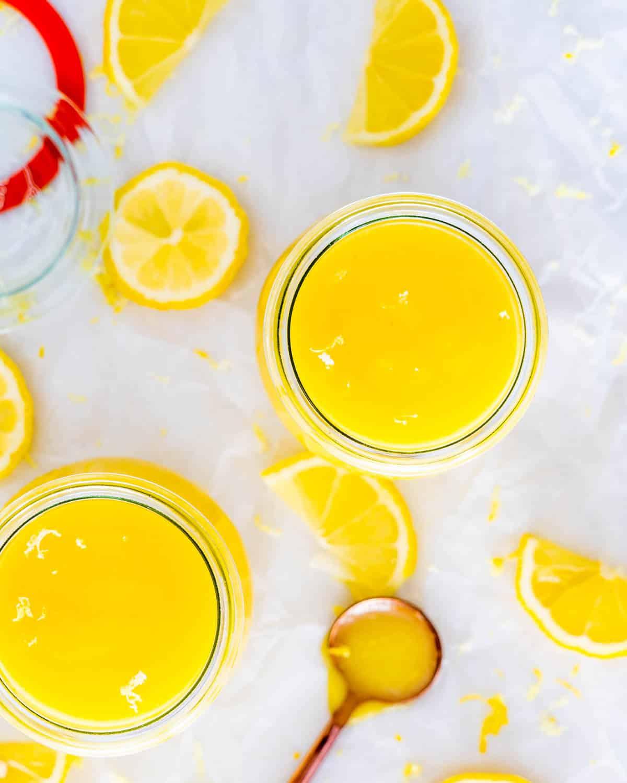 lemon curd in little jars with lemon slices around.