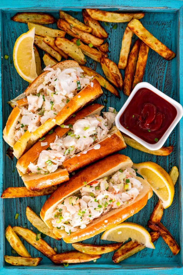3 lobster rolls on a blue tray with french fries around and garnished with lemon wedges.