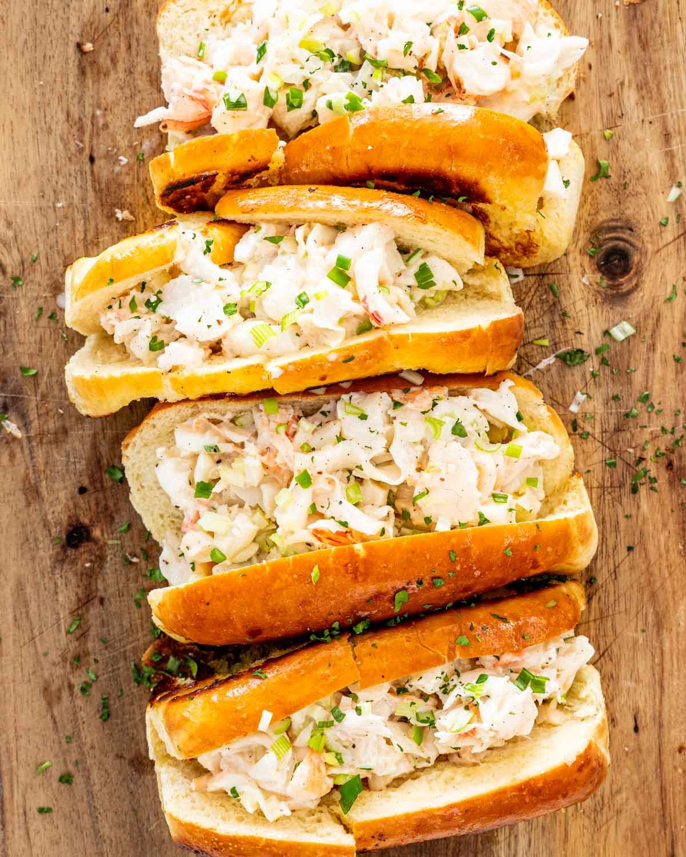 4 lobster rolls on a cutting board.