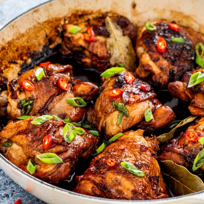 chicken adobo in a braiser garnished with green onions and red chilies.