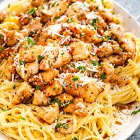 chicken scampi with linguini garnished with parmesan cheese on a white platter.