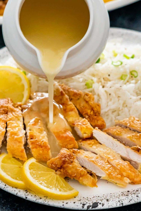pouring lemon sauce over fried chicken.