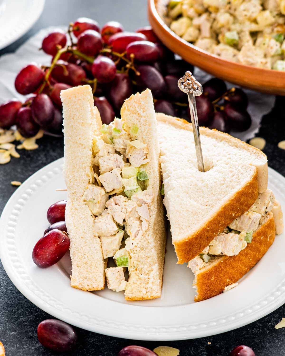 curry chicken salad sandwich cut in half on a white plate.