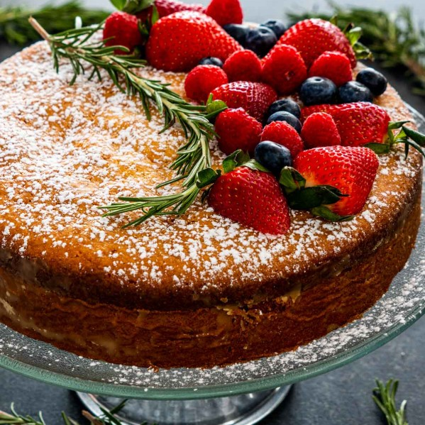 olive oil cake on a cake platter garnished with berries.