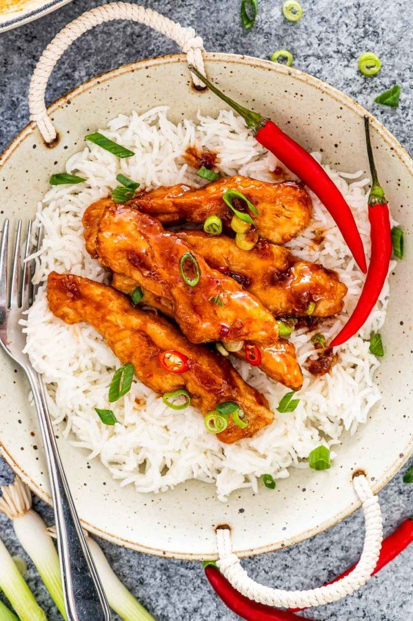 sweet chili chicken on a bed of rice garnished with green onions.