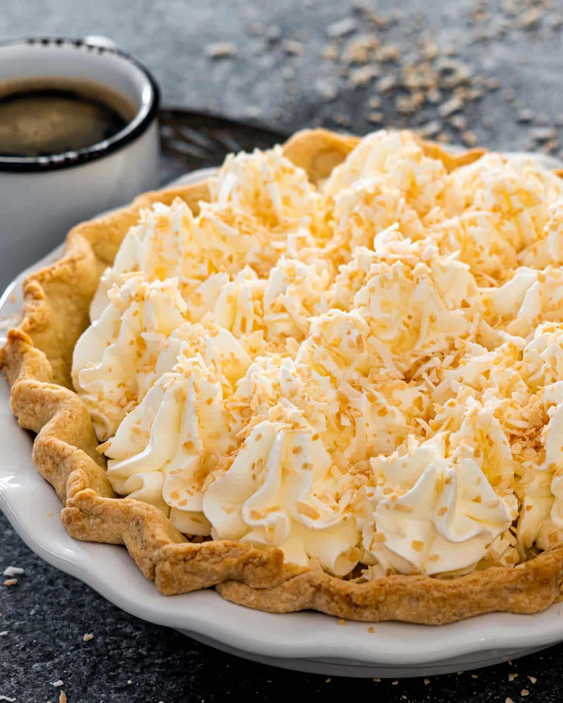 freshly made coconut cream pie on a pie plate.