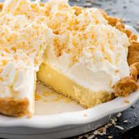 a coconut cream pie in a pie plate with a piece missing.