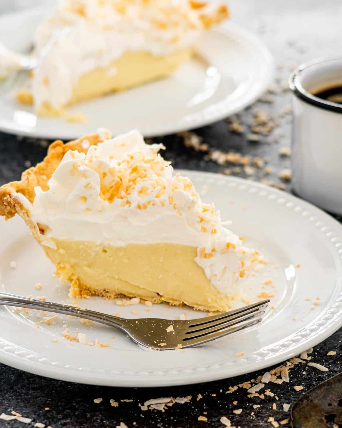 coconut cream pie slice on a white plate with a fork.