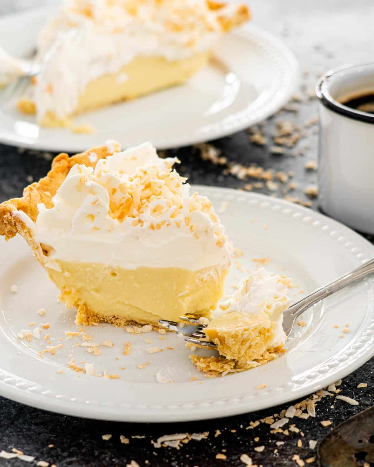 coconut cream pie slice on a white plate with a fork holding a bite.