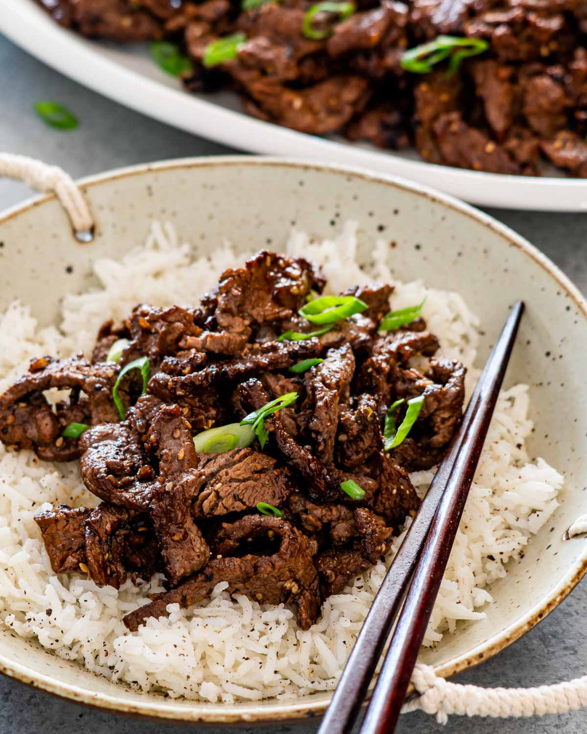 beef bulgogi over a bed of rice garnished with green onions.