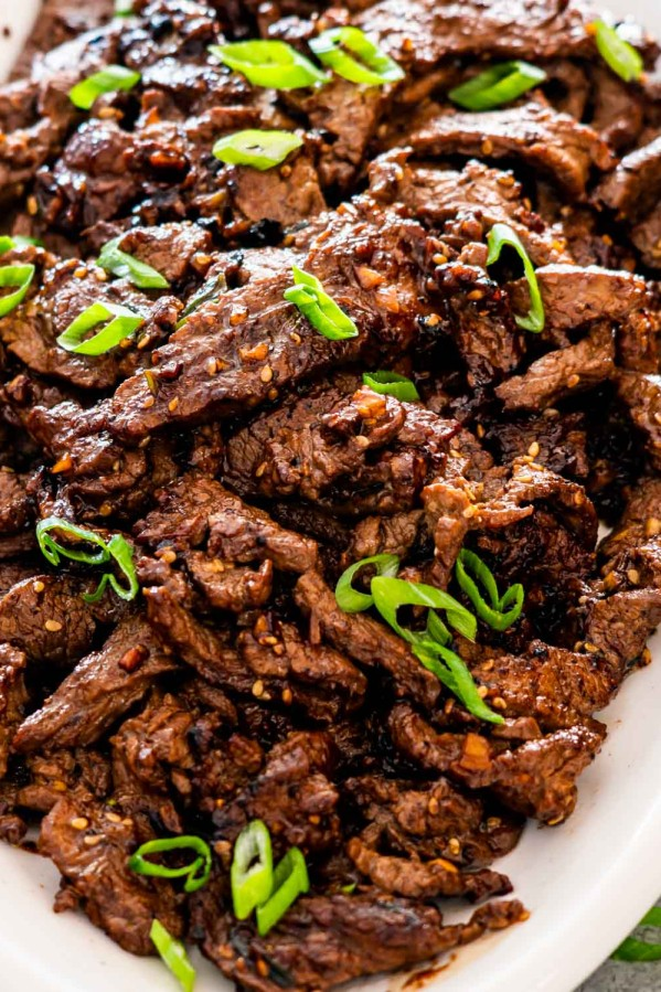 korean beef bulgogi garnished with green onions on a white serving platter.