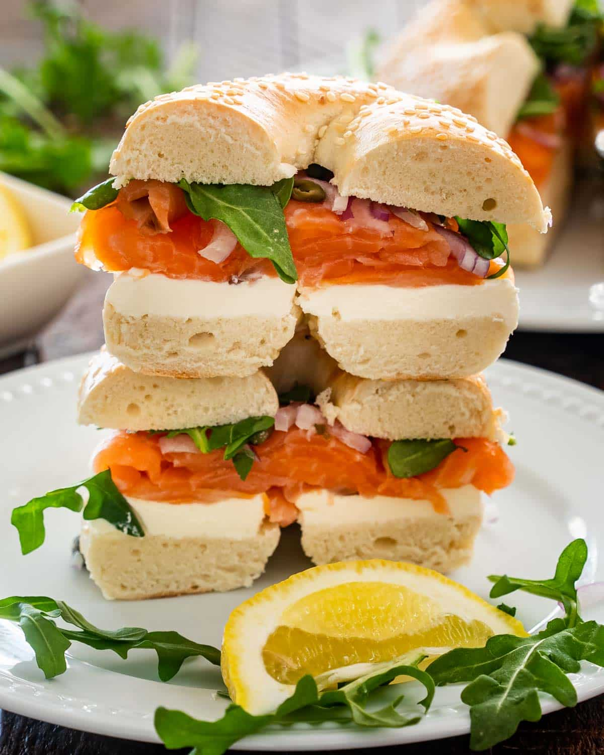 salmon cream cheese bagel on a white plate garnished with lemon wedge.