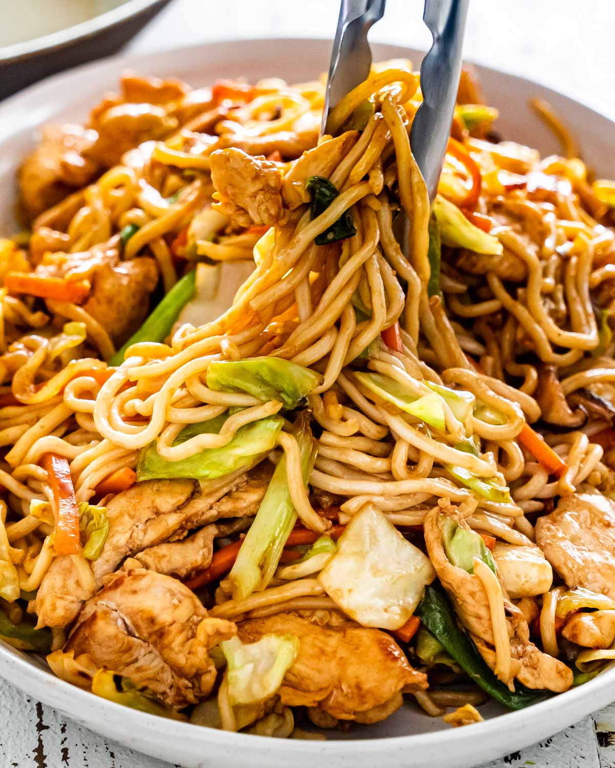 yakisoba noodles with chicken and vegetables in a large serving platter.