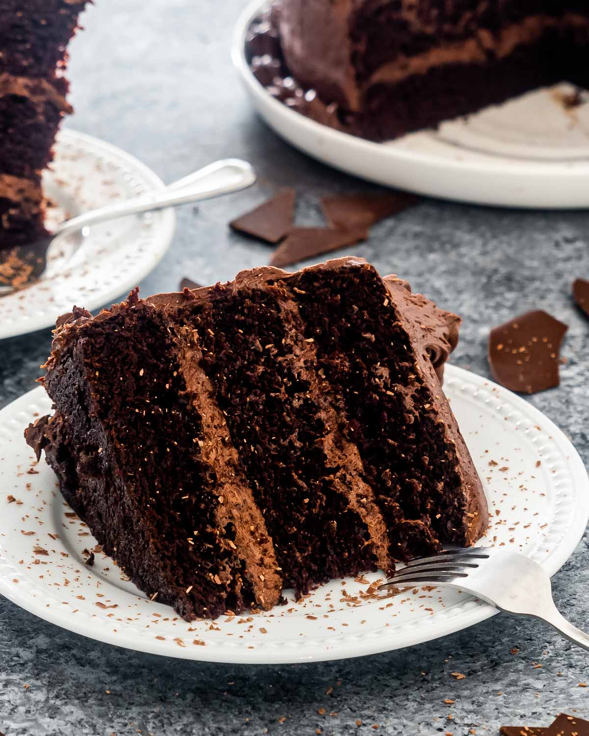 a bit slice of a 3 layer chocolate cake on a white plate.