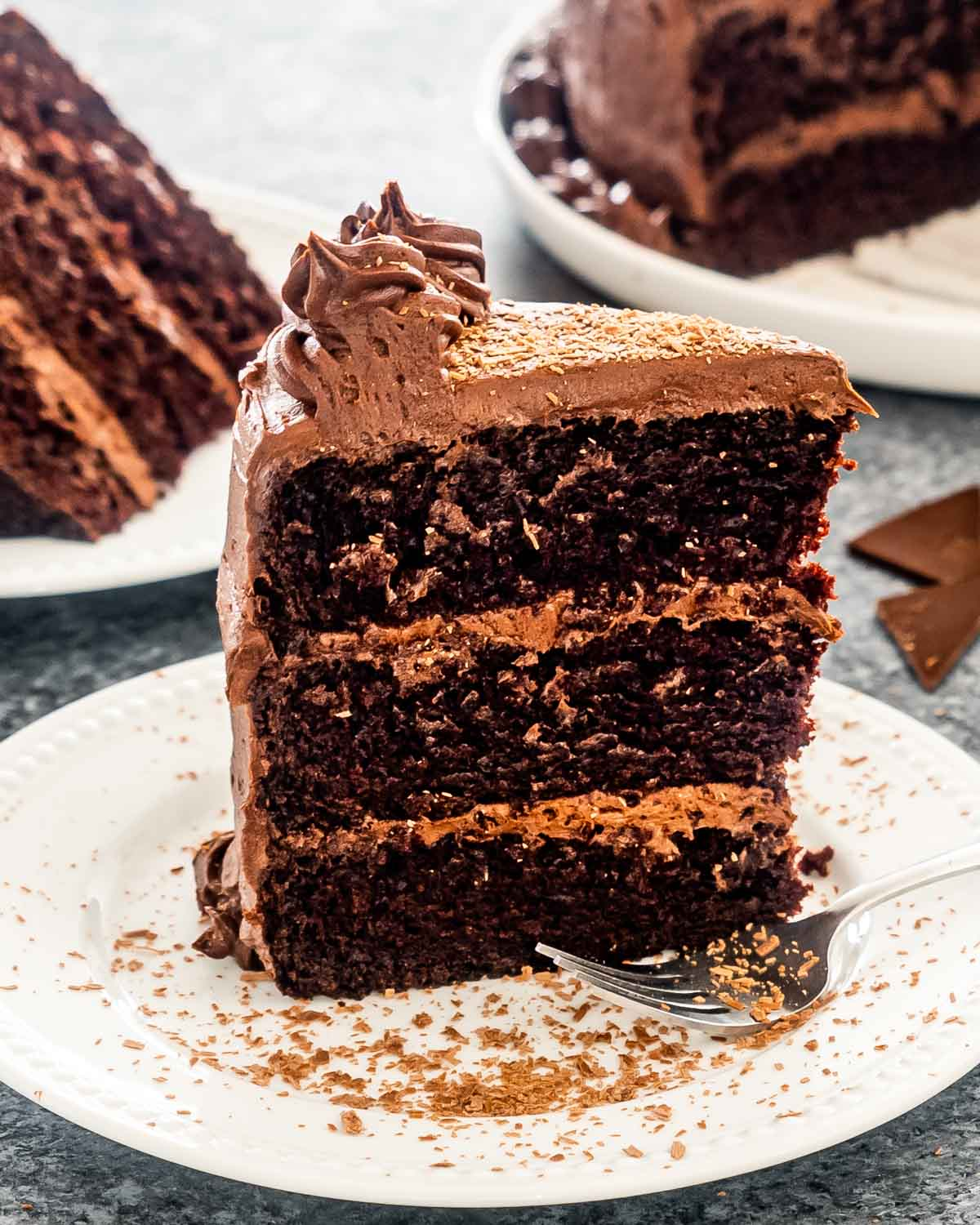 a big slice of a 3 layer chocolate cake on a white plate.