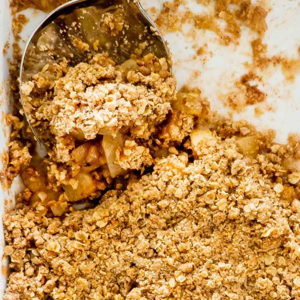 apple crumble in a baking dish with a serving spoon inside.