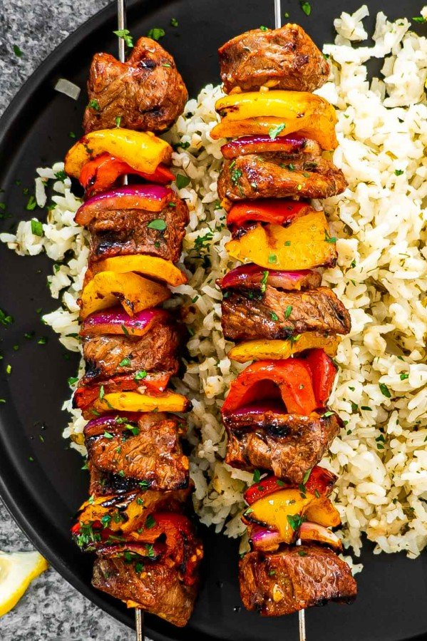 2 skewers of beef shish kebabs on a plate next to a bed of rice on a black plate.