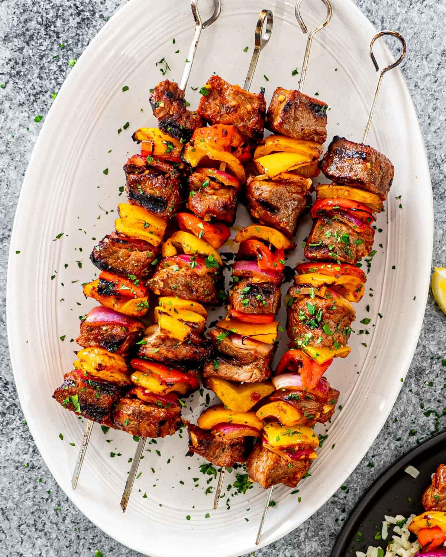 beef shish kebab skewers on a white serving platter.