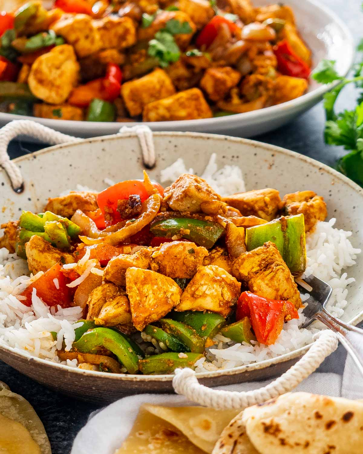 chicken jalfrezi on a plate with rice.