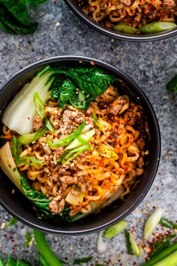 dan dan noodles in a black bowl.