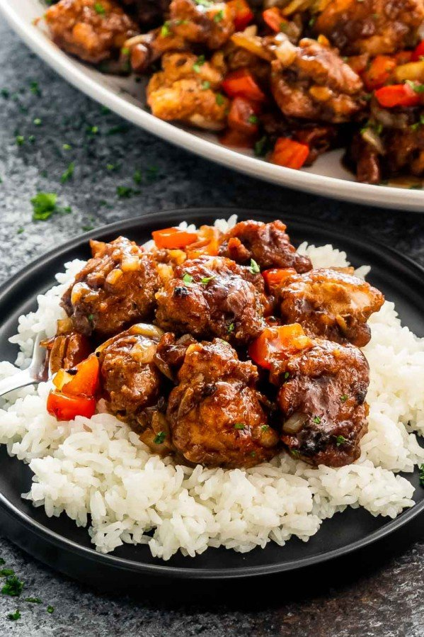 black pepper chicken on a bed of rice on a black plate.