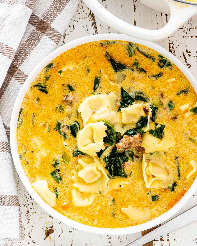 creamy tortellini soup in a white bowl.