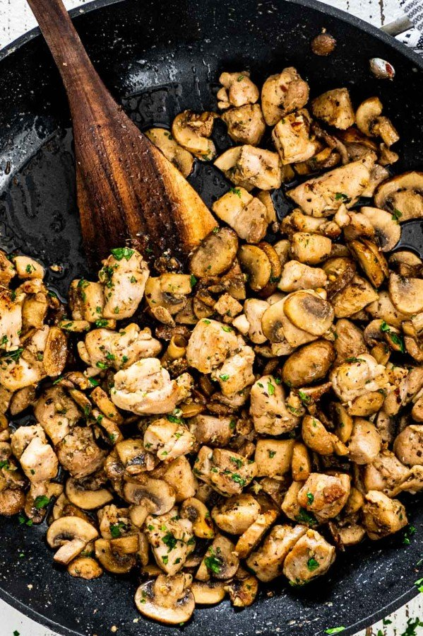 mushroom chicken bites in a black skillet with a wooden spatula in it.