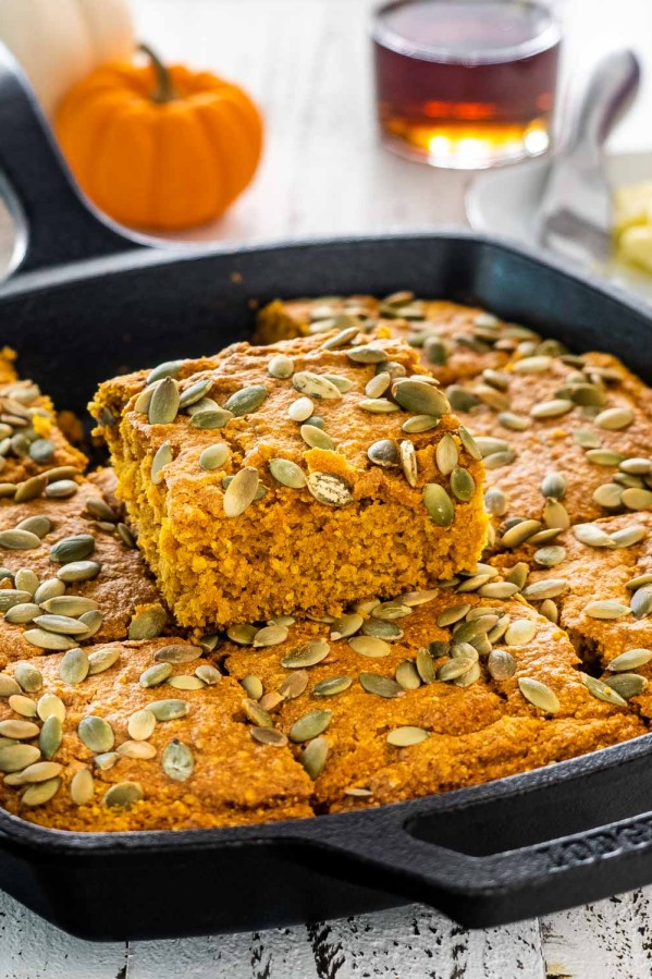 a skillet with pumpkin maple cornbread topped with pepitas and cut into slices.